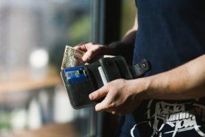 Foto von einer Person die Geld zahlt um zu verdeutlichen, dass der Immobilien-Eigentümer bei einer Sonderumlage noch einmal extra Geld zahlen muss. Eine Zahlung die der Immobilien-Eigentümer aus eigener Tasche zahlen muss.